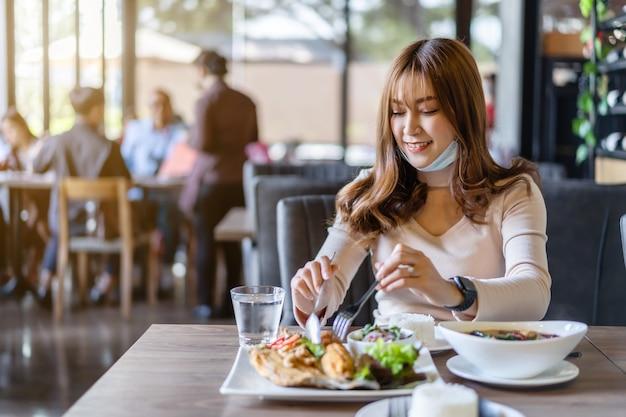 Mulher jovem com máscara facial comendo em restaurante, novo conceito normal para proteger a pandemia de coronavírus (covid-19)