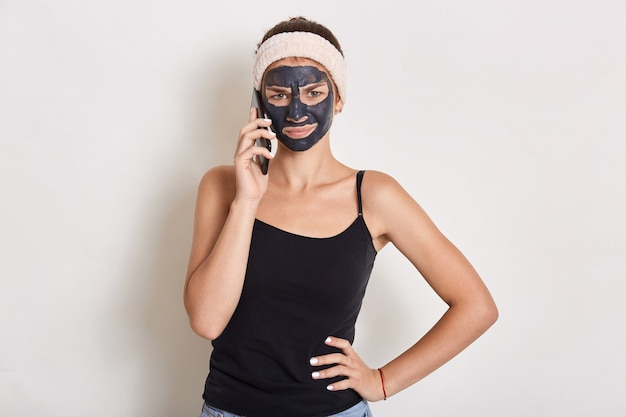 Mulher jovem com máscara facial de argila preta fazendo uma ligação