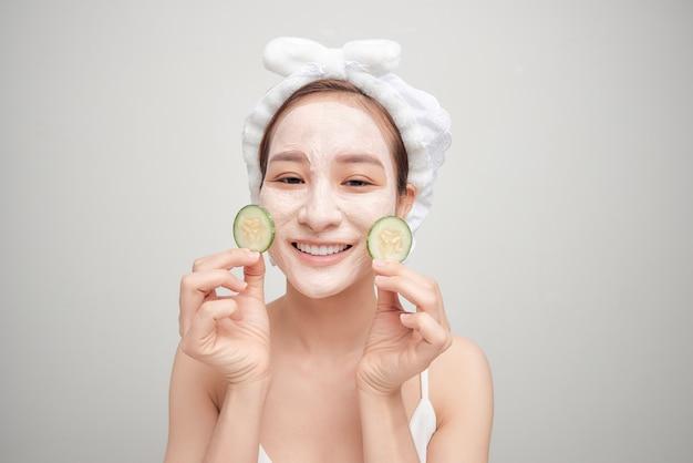 Mulher jovem com máscara facial de argila segurando fatias de pepino isoladas no fundo branco