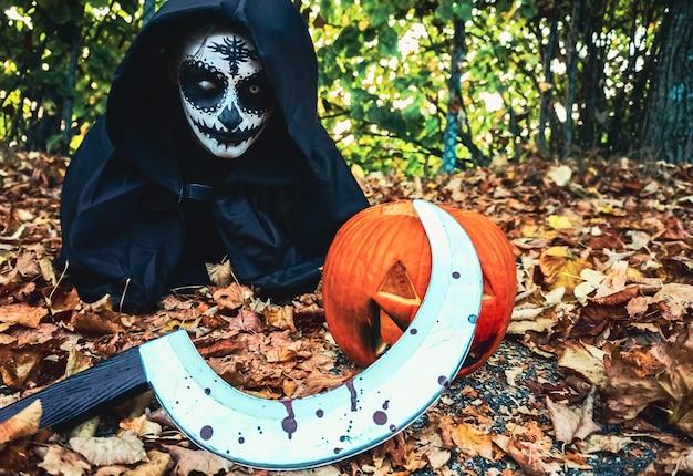 Mulher jovem com máscara facial de pintura de halloween e capuz preto