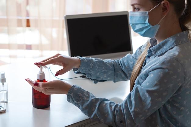 Mulher jovem com máscara facial desinfetando superfícies de gadgets em seu local de trabalho