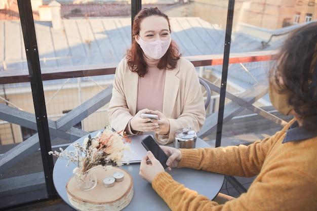 Mulher jovem com máscara falando com um rapaz enquanto eles estão sentados à mesa durante uma reunião no restaurante