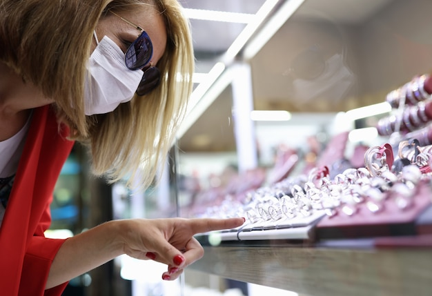 Mulher jovem com máscara médica, óculos de sol e jaqueta vermelha apontando o dedo para a exposição de joias