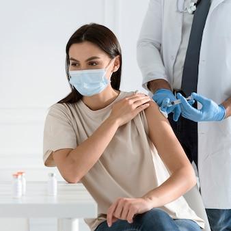 Mulher jovem com máscara médica sendo vacinada pelo médico