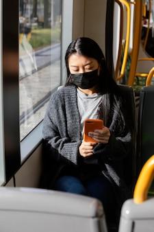 Mulher jovem com máscara no ônibus