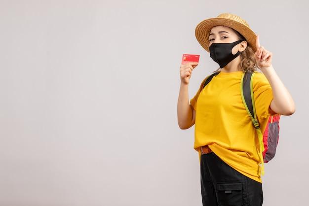Mulher jovem com máscara preta e mochila segurando um cartão