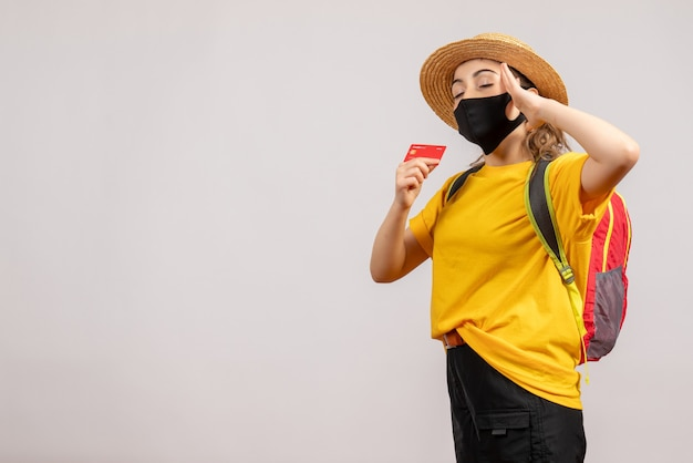 Mulher jovem com máscara preta fechando os olhos segurando um cartão