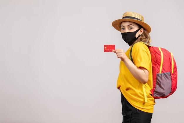 Mulher jovem com máscara preta segurando um cartão de vista frontal