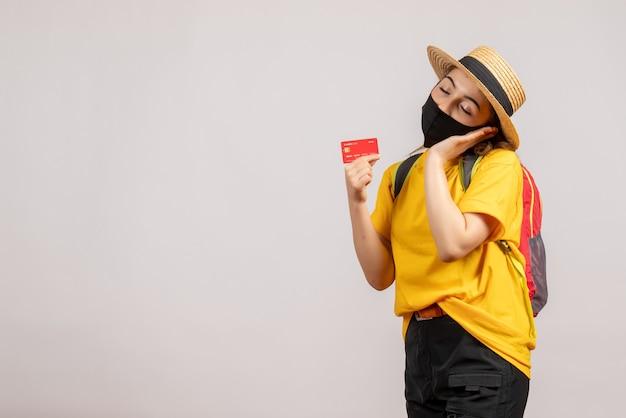 Mulher jovem com máscara preta segurando um cartão dormindo de frente