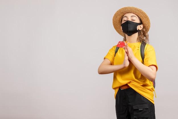 Mulher jovem com máscara preta segurando um cartão e as mãos juntas