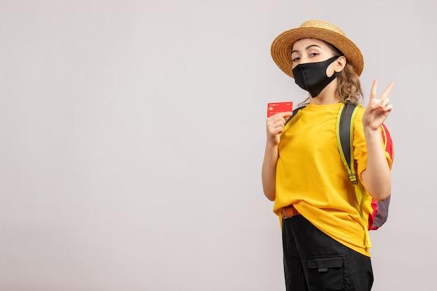 Mulher jovem com máscara preta segurando um cartão e fazendo o sinal da vitória