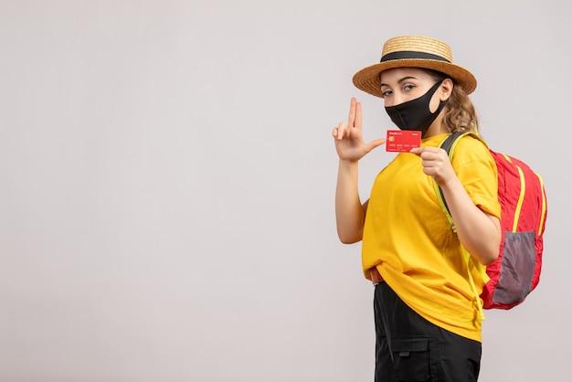 Mulher jovem com máscara preta segurando um cartão e fazendo uma arma de dedo de frente