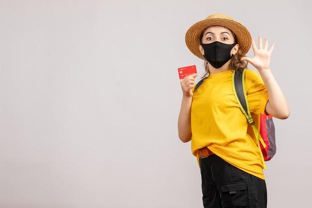 Mulher jovem com máscara preta segurando um cartão e saudando alguém