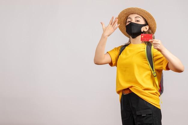 Mulher jovem com máscara preta segurando um cartão