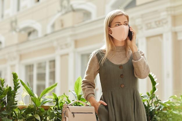Mulher jovem com máscara protetora conversa em seu telefone celular em um shopping