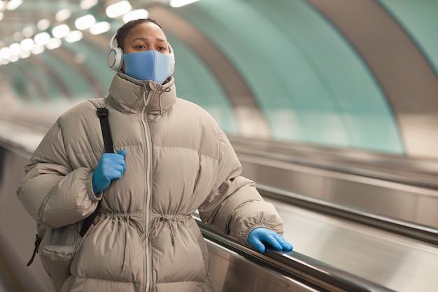 Mulher jovem com máscara protetora e luvas ouvindo música enquanto caminhava na escada rolante no aeroporto durante a pandemia