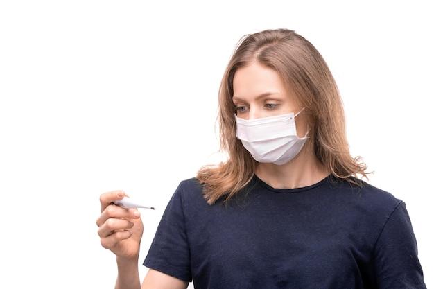 Mulher jovem com máscara protetora em pé e medindo a temperatura usando termômetro eletrônico