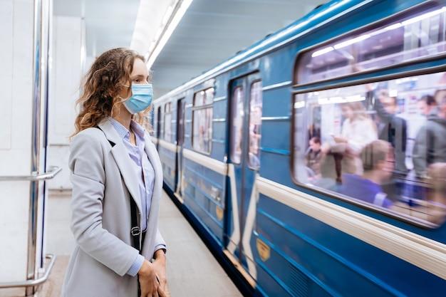 Mulher jovem com máscara protetora em pé na estação de metrô