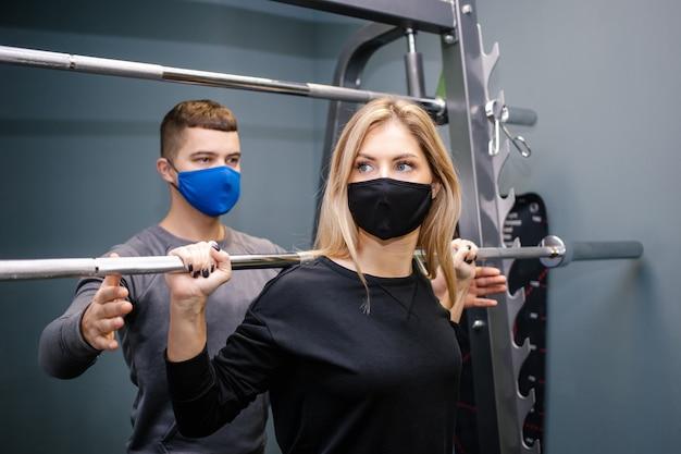 Mulher jovem com máscara protetora malhando com personal trainer na academia durante a pandemia de covid-19