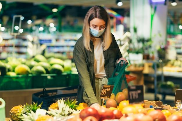 Mulher jovem com máscara protetora médica cara escolhe e escolhe em saco ecológico legumes ou frutas no supermercado mulher em pé em uma mercearia perto do balcão compra em um pacote reutilizável