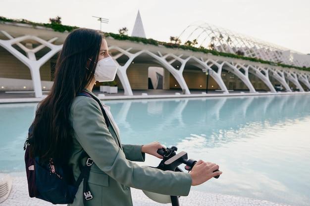 Mulher jovem com máscara protetora olhando para o horizonte enquanto segura uma scooter elétrica