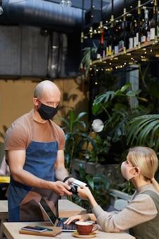 Mulher jovem com máscara protetora pagando com cartão de crédito o pedido ao garçom no café