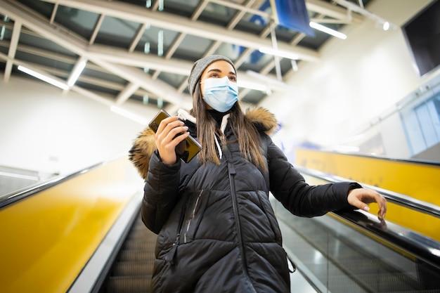Mulher jovem com máscara protetora subindo escadas em um aeroporto