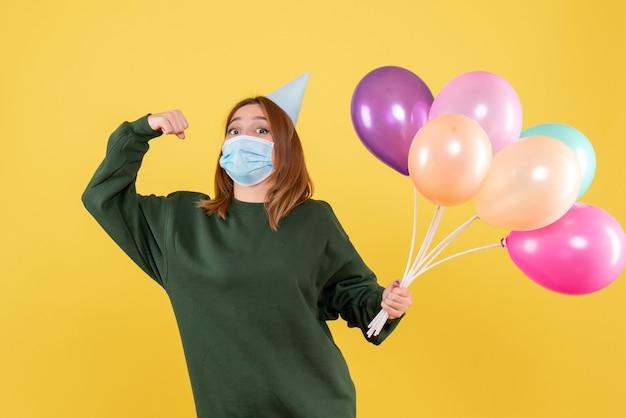 Mulher jovem com máscara segurando balões coloridos de frente