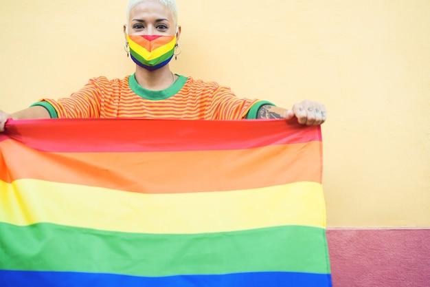 Mulher jovem com máscara segurando uma bandeira do arco-íris do orgulho gay