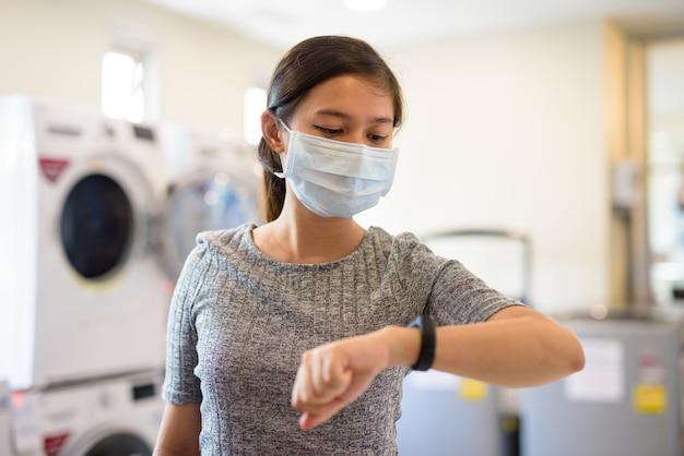 Mulher jovem com máscara, verificando as horas na lavanderia