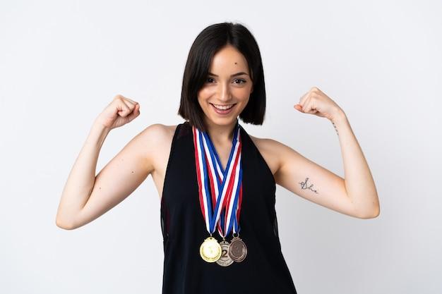 Mulher jovem com medalhas isoladas na parede branca comemorando vitória