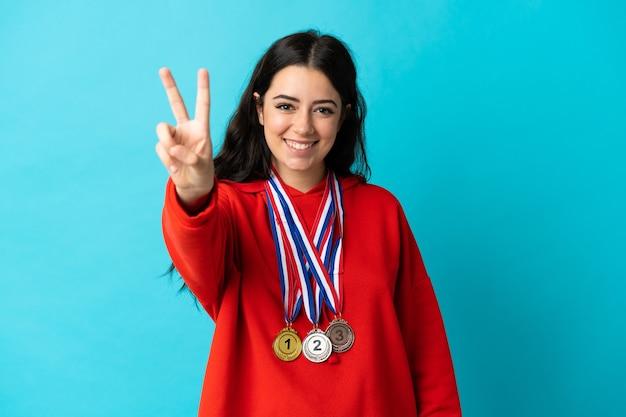 Mulher jovem com medalhas isoladas na parede branca sorrindo e mostrando o sinal da vitória