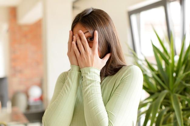 Mulher jovem com medo ou vergonha de espiar ou espiar com os olhos semicobertos pelas mãos