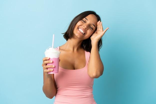 Mulher jovem com milk-shake de morango isolada em um fundo azul sorrindo muito