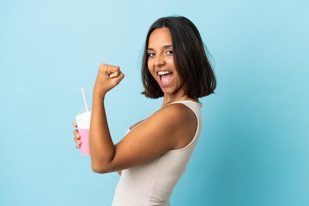 Mulher jovem com milk-shake de morango isolado no azul comemorando vitória