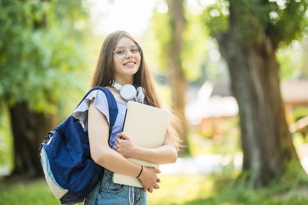 Mulher jovem com mochila caminhando pelo parque com laptop prateado nas mãos