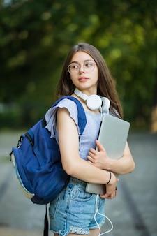 Mulher jovem com mochila caminhando pelo parque verde com laptop prateado nas mãos