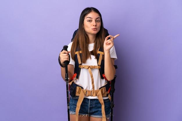 Mulher jovem com mochila e bastões de trekking isolados em roxo com a intenção de perceber a solução enquanto levanta um dedo