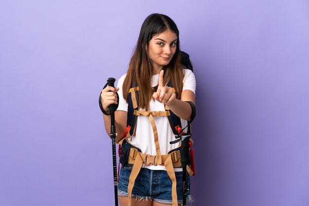 Mulher jovem com mochila e bastões de trekking isolados na parede roxa, mostrando e levantando um dedo
