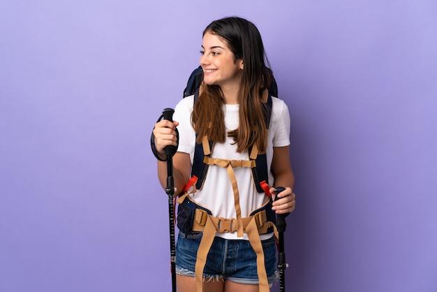 Mulher jovem com mochila e bastões de trekking isolados no lado roxo