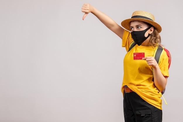 Mulher jovem com mochila segurando o cartão fazendo sinal de polegar para baixo