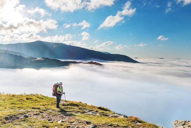 Mulher jovem com mochila viaja pelas montanhas