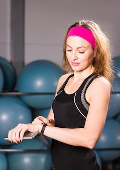 Mulher jovem com monitor de fitness no ginásio, pausa para treino