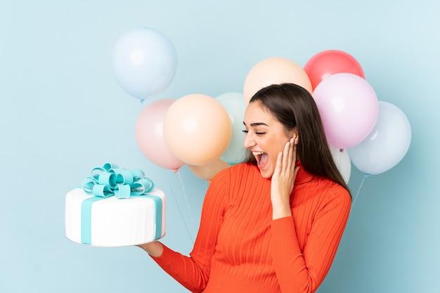 Mulher jovem com muitos balões isolados em fundo azul