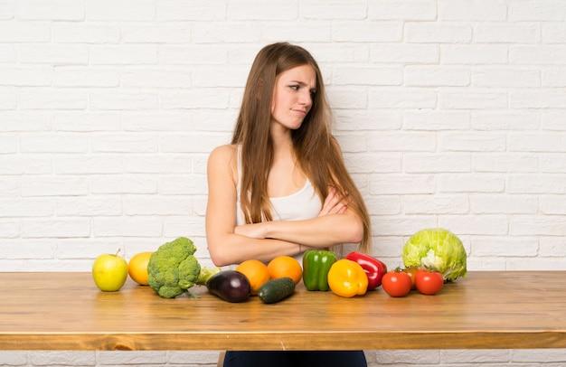 Mulher jovem, com, muitos, legumes, ficar, e, pensando uma idéia