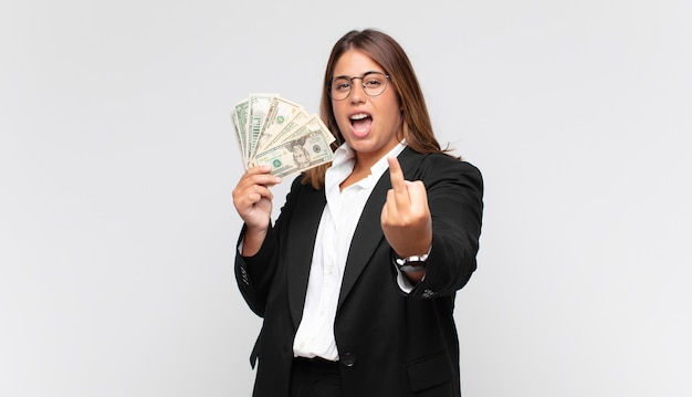 Mulher jovem com notas de dinheiro se sentindo irritada, irritada, rebelde e agressiva, sacudindo o dedo médio e revidando