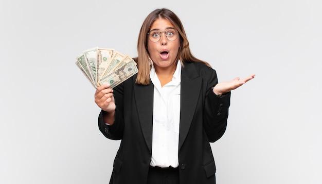 Mulher jovem com notas de dinheiro sentindo-se extremamente chocada e surpresa, ansiosa e em pânico, com um olhar estressado e horrorizado