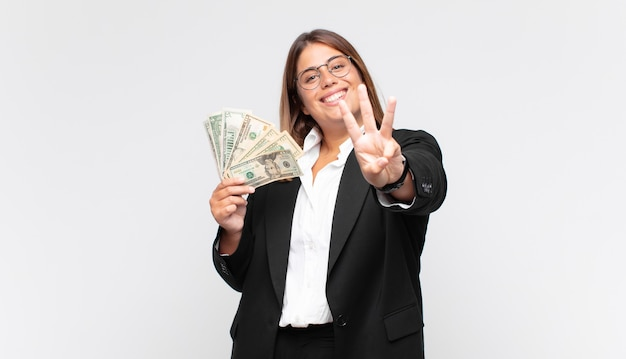 Mulher jovem com notas, sorrindo e parecendo amigável, mostrando o número três ou terceiro com a mão para a frente, em contagem regressiva