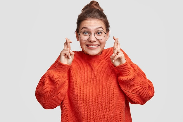 Mulher jovem com o cabelo preso em um coque e um suéter grande