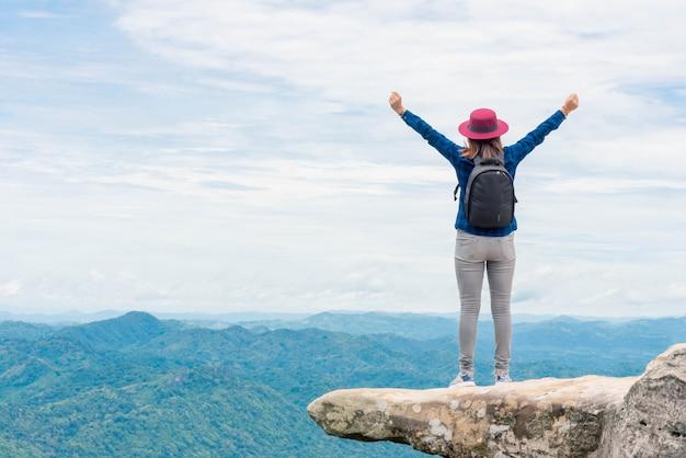 Mulher jovem com o sucesso no ponto mais alto - conceito de sucesso